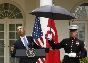 U.S. President Obama checks the need for and umbrella held by a U.S. Marine during a joint news conference with Turkish Prime Minister Erdogan in Washington