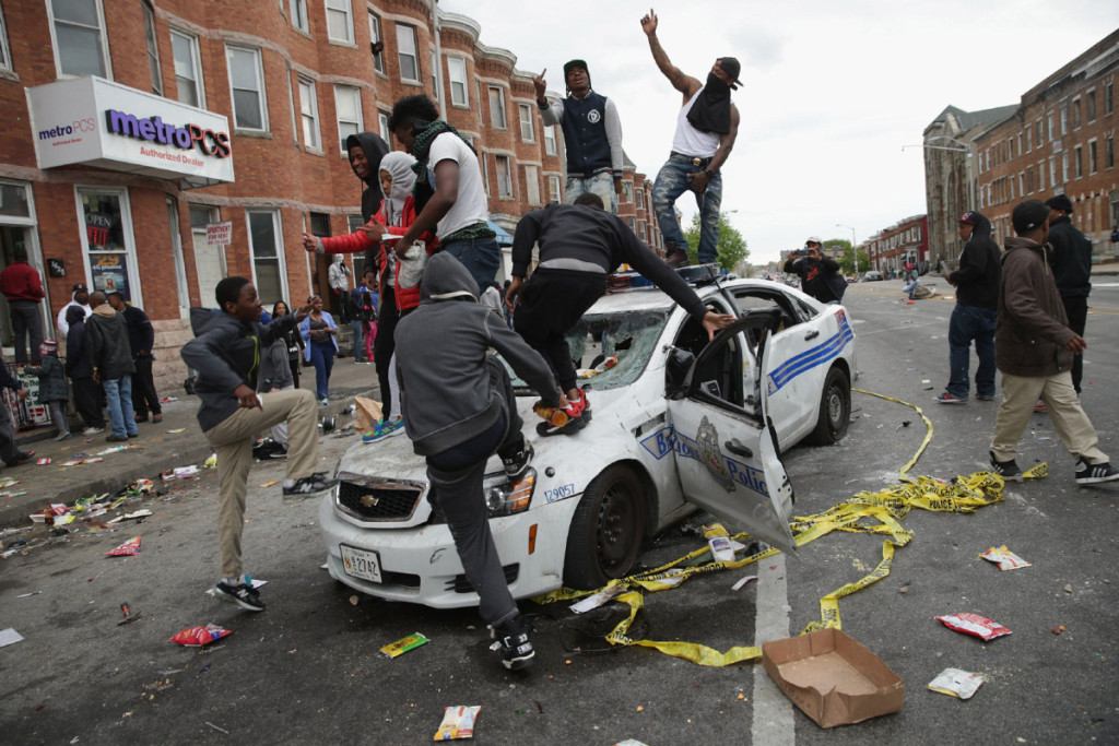 BESTPIX BALTIMORE, MD - APRIL 27:  Demonstrators climb on a destroyed Baltimore Police car in the street near the corner of Pennsylvania and North avenues during violent protests following the funeral of Freddie Gray April 27, 2015 in Baltimore, Maryland. Gray, 25, who was arrested for possessing a switch blade knife April 12 outside the Gilmor Homes housing project on Baltimore's west side. According to his attorney, Gray died a week later in the hospital from a severe spinal cord injury he received while in police custody.  (Photo by Chip Somodevilla/Getty Images) *** BESTPIX ***